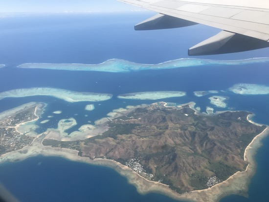 View from airplane on a flight from Fiji to the Solomon Islands. Shows green island, blue ocean, and airplane wing.